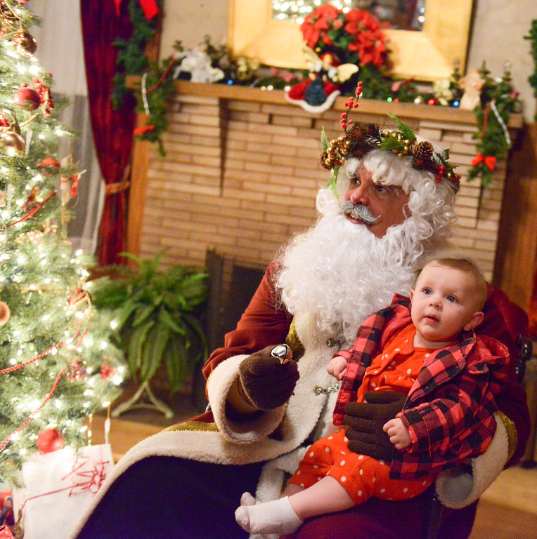 Justin Sheely | The Sheridan Press<br /> Father Christmas holds 9-month-old Victoria Gaball during the Holiday Open House at the Trail End State Historic Site Friday evening. Festivities at site, also called Kendrick Mansion, included guest performances, figgy pudding and a visit from Father Christmas.