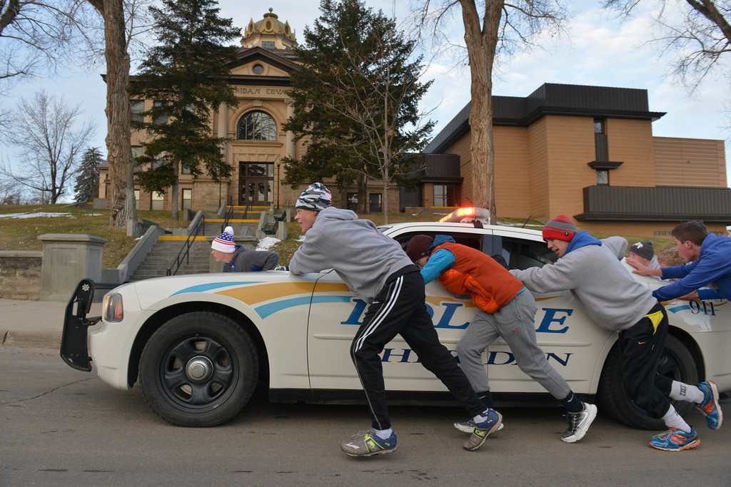 Justin Sheely | The Sheridan Press<br /> The Sheridan Broncs wrestling team push a Sheridan Police Department cruiser up the hill past the Sheridan County Courthouse Saturday morning to kickoff practice for the season. The team pushed the cruiser, weighing approximately 4300 pounds, almost 3 miles from the police station to the courthouse and back.