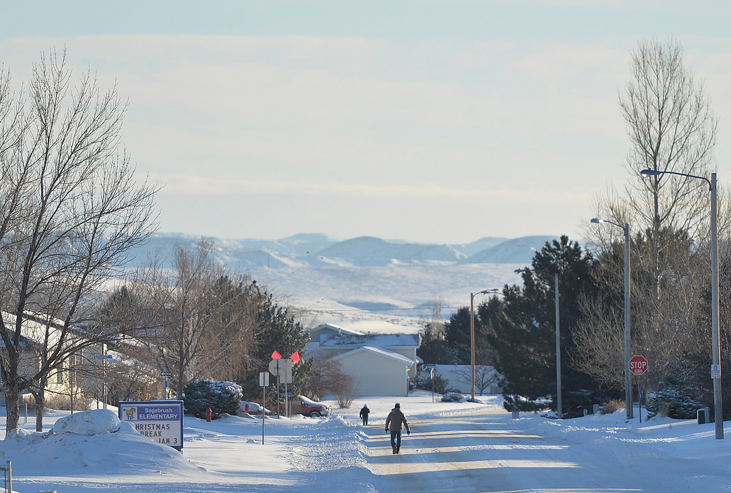 Justin Sheely | The Sheridan Press<br /> People walk down Hill Pond Drive Monday morning in Sheridan. A winter blizzard dumped 5 to 7 inches of snow in the city of Sheridan over Christmas Day. Story reported up to 12 inches of snow.