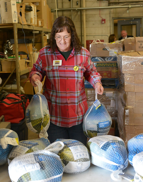 Justin Sheely | The Sheridan Press<br /> Tammy Ward places out frozen turkeys during the Wyoming Food Bank of the Rockies holiday meal box distribution Tuesday at Powder River Energy Corporation. The Casper-based non profit sent their mobile unit to Sheridan to provide meals for up to 300 households. The distribution was made possible with grants from WYO Coal, Powder River Energy Corporation and donations from the Sheridan County community.
