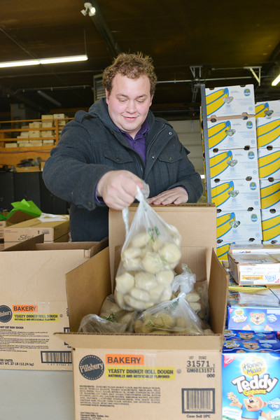 Justin Sheely | The Sheridan Press<br /> Powder River Energy employee Christian Klepperich unpacks boxes of food during the Wyoming Food Bank of the Rockies holiday meal box distribution Tuesday at Powder River Energy Corporation. The Casper-based non profit sent their mobile unit to Sheridan to provide meals for up to 300 households. The distribution was made possible with grants from WYO Coal, Powder River Energy Corporation and donations from the Sheridan County community.