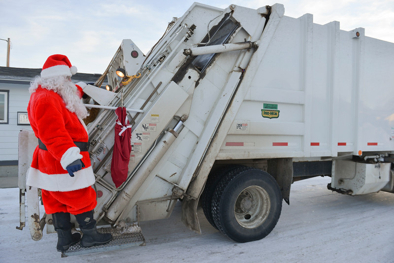 Justin Sheely | The Sheridan Press<br /> Town of Ranchester employee Robert Miller, as Santa Claus, rides the back of the garbage truck Friday morning in Ranchester. Waste Management staff wore festive costumes while collecting garbage bins around town.