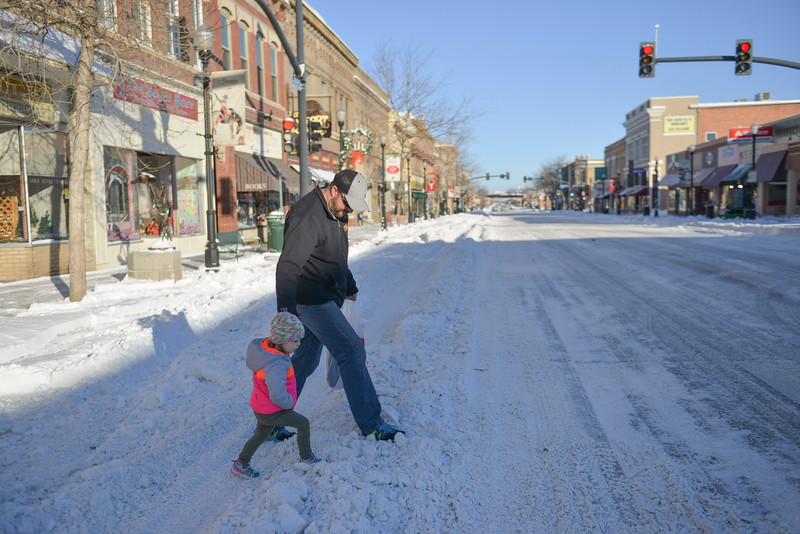 Justin Sheely | The Sheridan Press<br /> Travis Pepin helps his daughter Skylar Pepin, 2, across Main Street Monday morning in Sheridan. A winter blizzard dumped 5 to 7 inches of snow in the city of Sheridan over Christmas Day. Story reported up to 12 inches of snow.