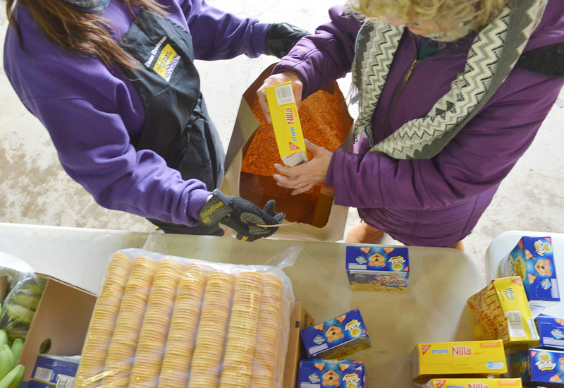 Justin Sheely | The Sheridan Press<br /> A food bank worker, left, helps a community member load up a meal package during the Wyoming Food Bank of the Rockies holiday meal box distribution Tuesday at Powder River Energy Corporation. The Casper-based non profit sent their mobile unit to Sheridan to provide meals for up to 300 households. The distribution was made possible with grants from WYO Coal, Powder River Energy Corporation and donations from the Sheridan County community.