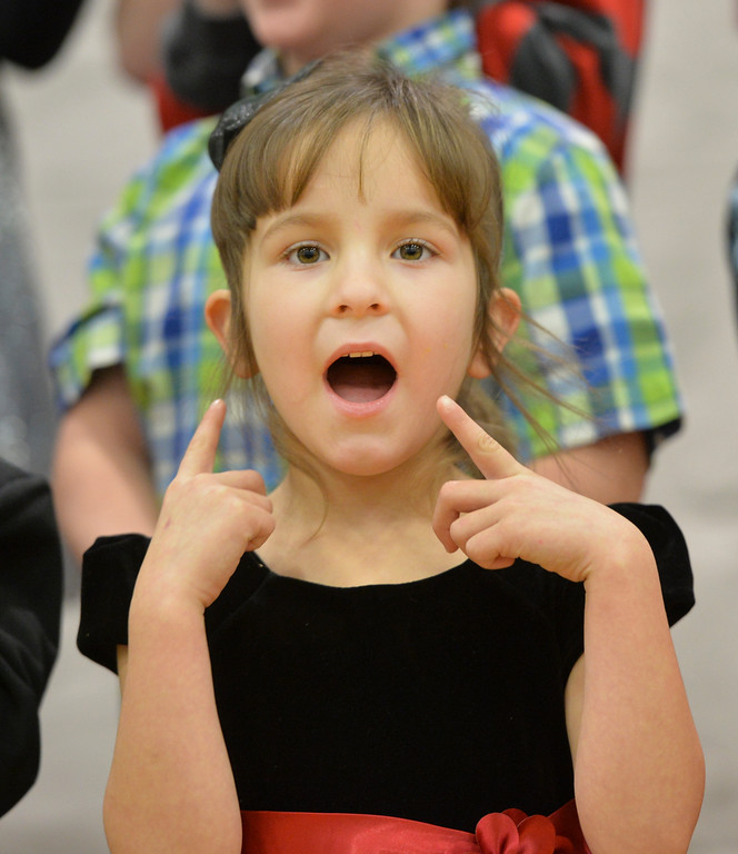 Justin Sheely | The Sheridan Press<br /> Kindergartener Presley Vigil gestures to her mouth as she sings during the Christmas program Tuesday at Coffeen Elementary School.