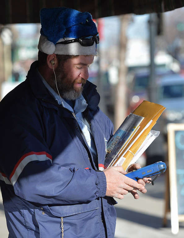 Justin Sheely | The Sheridan Press<br /> United States Post Office carrier Matthew Vielhauer delivers to businesses on Main Street Saturday in downtown Sheridan.