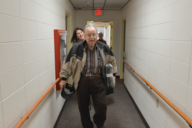 Justin Sheely | The Sheridan Press<br /> Brookdale Sugar Land Ridge resident Pete Welty marches up a hallway with a blanket tucked under his arm at Heritage Towers on Wednesday. Residents from Sugar Land Ridge donated blankets along with canned and boxed foods to 23 individual seniors living in Sheridan and Dayton. The generous gifting was the idea of Brookdale Living resident Barbara Oedekoven, who said there is a need to provide for seniors without families in the area. The residents hope to make the holiday giving an annual event.