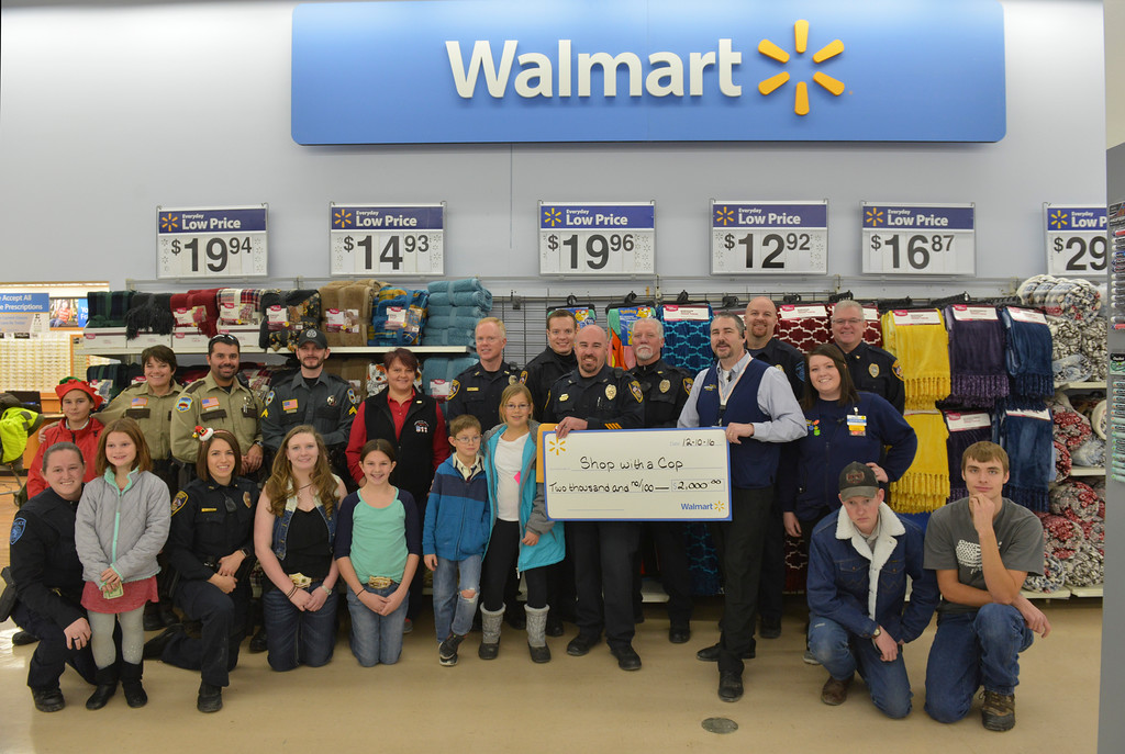 Justin Sheely | The Sheridan Press<br /> Wal-Mart issued a grant for $2,000 for the Shop with a Cop program, which helps deserving children provide gifts for their families. The program works with local school resource officers to determine which students need help this holiday season. More than 50 children shopped for gifts with the Sheridan Police Department, Sheridan County Sheriff's office, Wyoming Highway Patrol and the Sheridan College Police.