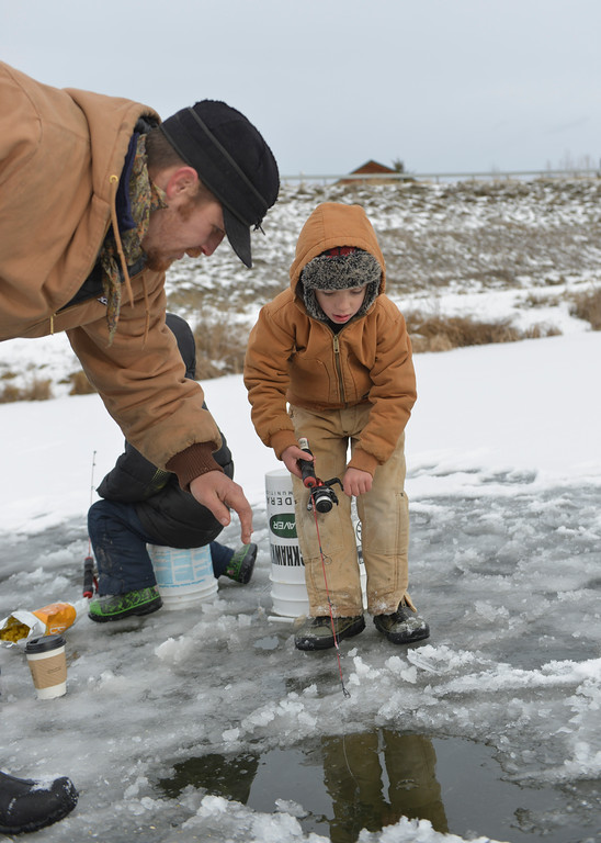 Justin Sheely | The Sheridan Press<br /> Ray Hahn helps his son Elijah Balkenbush, 6, ice fish Saturday morning at Sam Mavrakis Pond in Sheridan.