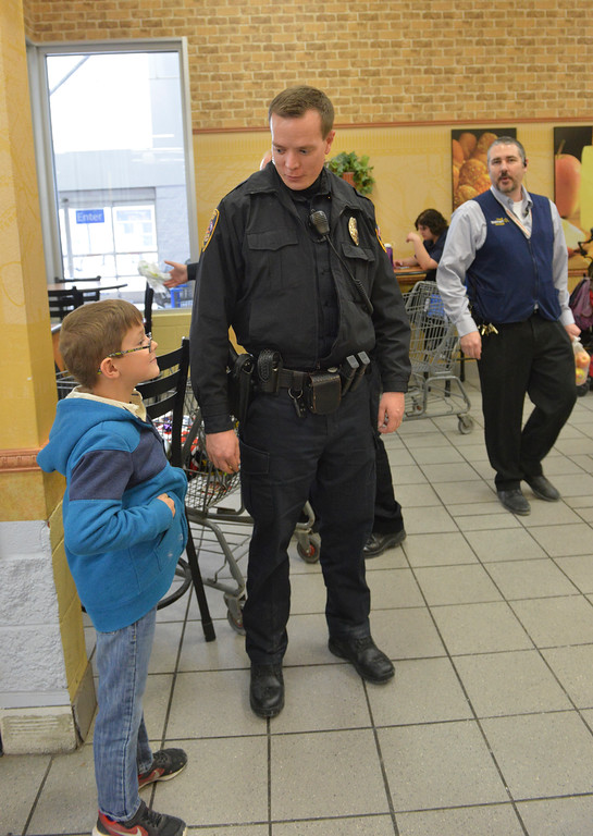 Justin Sheely | The Sheridan Press<br /> Seven-year-old Sam Wilsock waits with Sheridan Police Sergeant James Hill for a sandwich at Subway during Shop with a Cop Saturday at the Sheridan Wal-Mart store. Wal-Mart issued a grant for $2,000 for the program, which helps deserving children provide gifts for their families. The program works with local school resource officers to determine which students need help this holiday season. More than 50 children shopped for gifts with the Sheridan Police Department, Sheridan County Sheriff's office, Wyoming Highway Patrol and the Sheridan College Police.