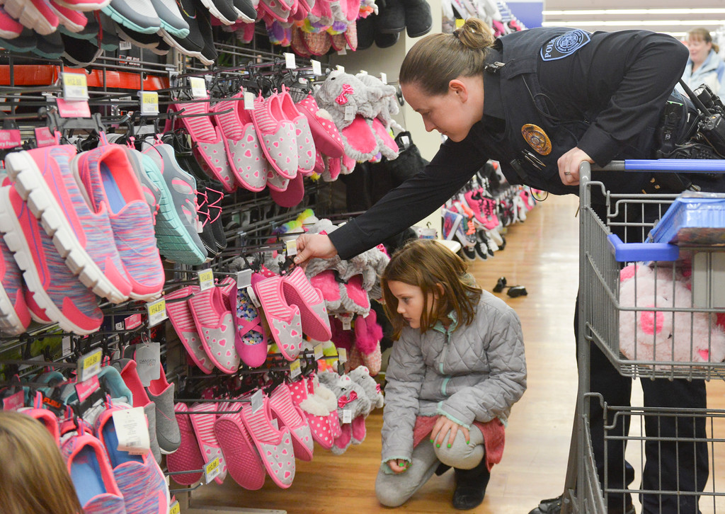 Justin Sheely | The Sheridan Press<br /> Seven-year-old Elizabeth Oaks shops for gifts with Sheridan College officer Kayliegh O'Bryant during Shop with a Cop Saturday at the Sheridan Wal-Mart store. Wal-Mart issued a grant for $2,000 for the program, which helps deserving children provide gifts for their families. The program works with local school resource officers to determine which students need help this holiday season. More than 50 children shopped for gifts with the Sheridan Police Department, Sheridan County Sheriff's office, Wyoming Highway Patrol and the Sheridan College Police.