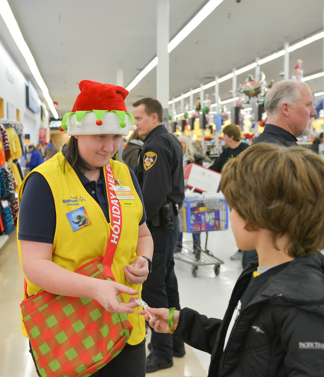 Justin Sheely | The Sheridan Press<br /> Store cashier Brittney Hill offers candy during Shop with a Cop Saturday at the Sheridan Wal-Mart store. Wal-Mart issued a grant for $2,000 for the program, which helps deserving children provide gifts for their families. The program works with local school resource officers to determine which students need help this holiday season. More than 50 children shopped for gifts with the Sheridan Police Department, Sheridan County Sheriff's office, Wyoming Highway Patrol and the Sheridan College Police.
