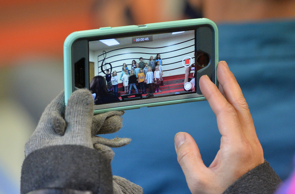 Justin Sheely | The Sheridan Press<br /> A parent records video on a cellphone during the Kids Chorus program Thursday at the YMCA. The program is offered for kids Kindergarten through third grade to learn the foundations of music. The program resumes in January at the YMCA.