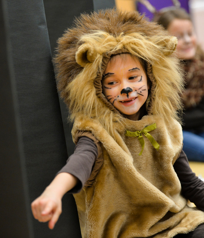 Justin Sheely | The Sheridan Press<br /> First-grader Constance Merriam, as a lion, answers questions from a visitor during the Animal Wax Museum Wednesday at Woodland Park Elementary School. Each student picked an animal, did their own research and compiled facts for their projects. The students created their poster boards and dressed as their animals to present their research to parents, teachers, faculty, students and other visitors during Wednesday's event.
