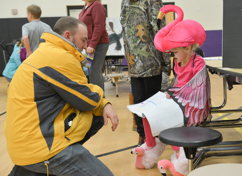 Justin Sheely | The Sheridan Press<br /> Getty Babbitt, left, listens as Gabby Koval reads facts about flamingos during the Animal Wax Museum Wednesday at Woodland Park Elementary School. Each student picked an animal, did their own research and compiled facts for their projects. The students created their poster boards and dressed as their animals to present their research to parents, teachers, faculty, students and other visitors during Wednesday's event.