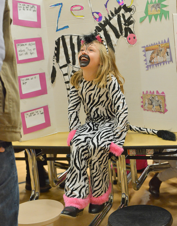 Justin Sheely | The Sheridan Press<br /> First-grader Tori Hunter, as a zebra, answers questions from a visitor during the Animal Wax Museum Wednesday at Woodland Park Elementary School. Each student picked an animal, did their own research and compiled facts for their projects. The students created their poster boards and dressed as their animals to present their research to parents, teachers, faculty, students and other visitors during Wednesday's event.