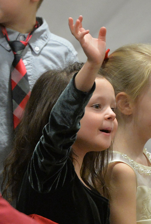 "Justin Sheely | The Sheridan Press<br /> Kindergartener Kelsie Adamson waves to her family during ""Sounds of the Season"" holiday program Tuesday at Woodland Park Elementary School."