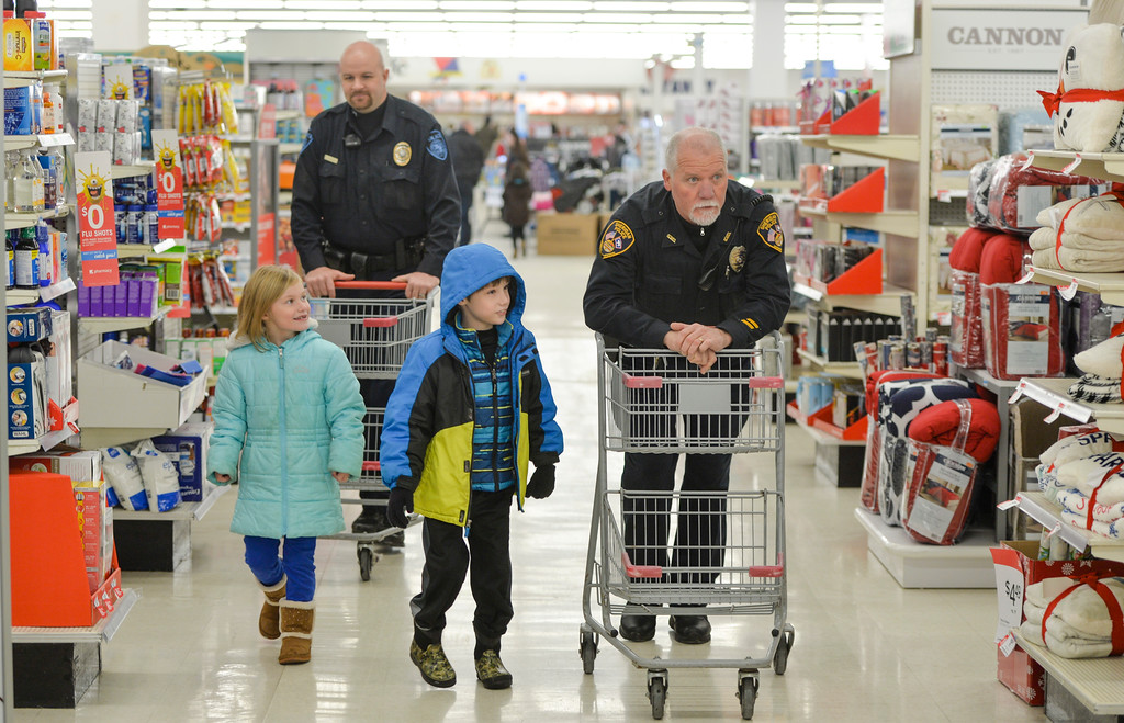 "Justin Sheely | The Sheridan Press<br /> Children, from left, Delaney Morel, 6, and Gavin Morel, 9, walk up with Sheridan College officer Josh McKinley, left, and Sheridan Police Officer Randy Pitchford during ""Shop with a Cop"" Saturday at Kmart. Several local law enforcement agencies partnered with the Food Bank for the annual event to help children provide Christmas gifts for their family."