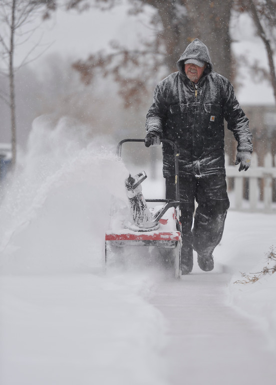 Justin Sheely | The Sheridan Press<br /> Terry Garrison, with the Sheridan Senior Center, runs a snowblower down the sidewalk for neighbors Friday morning on Smith Street in Sheridan.