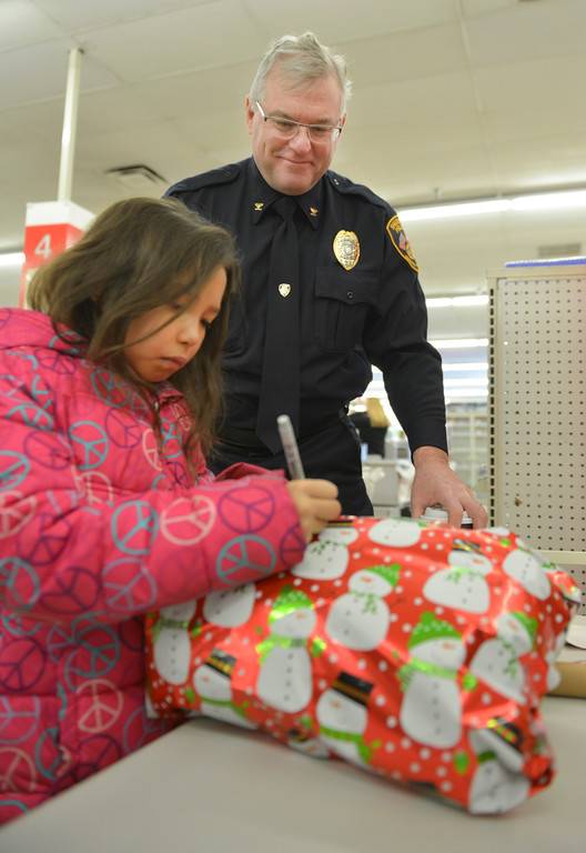 "Justin Sheely | The Sheridan Press<br /> Sheridan Police Chief Richard Adriaens looks on as Jasmine Beasley, 9, writes a tag for her gift during ""Shop with a Cop"" Saturday at Kmart. Several local law enforcement agencies partnered with the Food Bank for the annual event to help children provide Christmas gifts for their family."