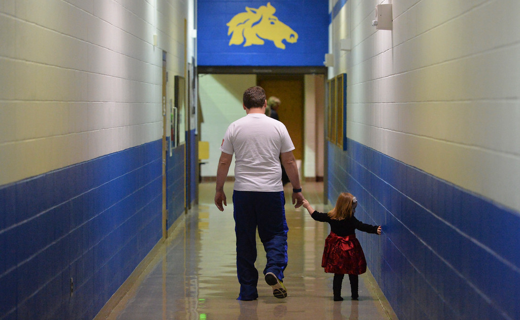 "Justin Sheely | The Sheridan Press<br /> Paul Phillips walks with his daughter Sadie Phillips, 2, in the hallways during the Band Department's ""A Very Merry Christmas"" concert Thursday at Sheridan High School."