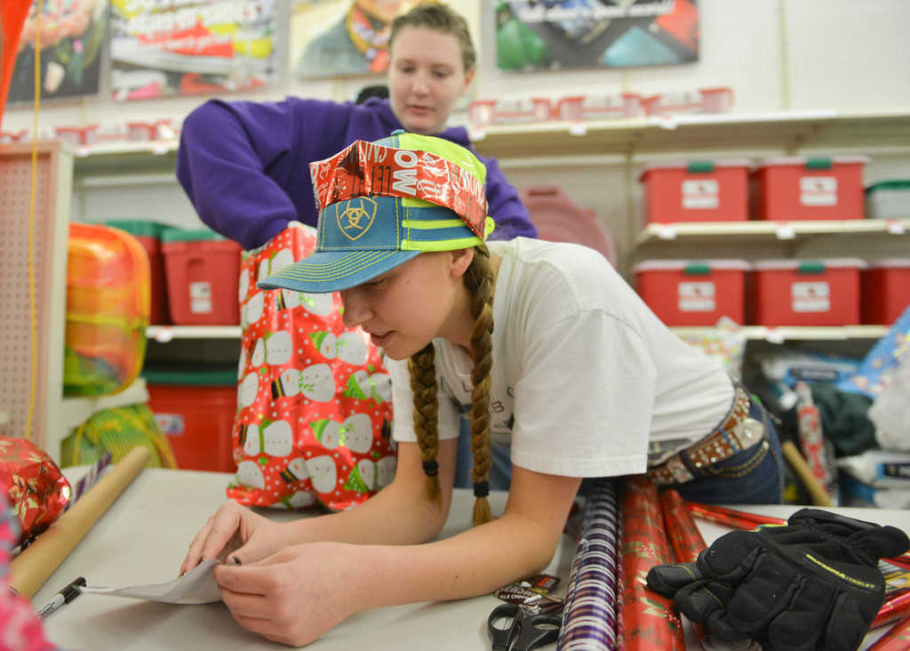"Justin Sheely | The Sheridan Press<br /> 4-H club volunteers Samantha Lamb, top, and Kace Pearce wrap gifts for children during ""Shop with a Cop"" Saturday at Kmart. Several local law enforcement agencies partnered with the Food Bank for the annual event to help children provide Christmas gifts for their family."