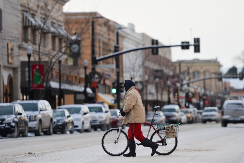Justin Sheely | The Sheridan Press<br /> A person pushes a bike across snow-packed Main Street Wednesday morning. <br /> The National Weather Service has issued a winter storm warning effective through Friday night, which says to expect 6 to 10 inches of snow.