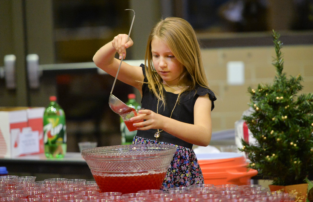 Justin Sheely | The Sheridan Press<br /> Ten-year-old Naomi Andersen serves punch for guests during the band concert Thursday at Sheridan High School.