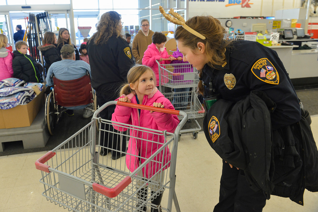 "Justin Sheely | The Sheridan Press<br /> Six-year-old Stella Forman talks with Sheridan Police officer Meagan Phillips during ""Shop with a Cop"" Saturday at Kmart. Several local law enforcement agencies partnered with the Food Bank for the annual event to help children provide Christmas gifts for their family."