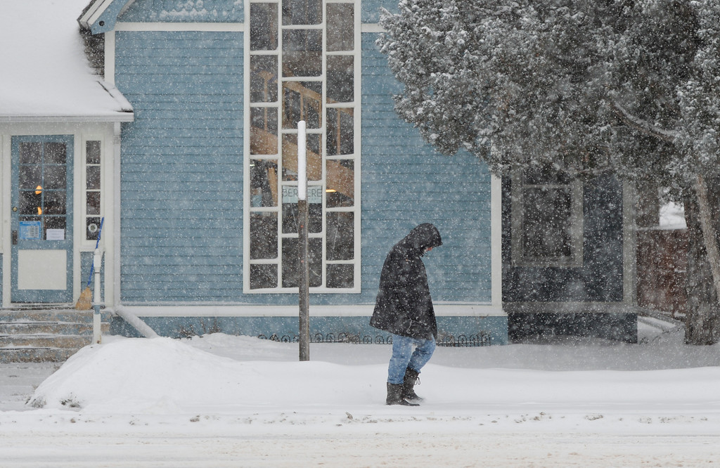 Justin Sheely | The Sheridan Press<br /> A person walks down Coffeen Avenue Friday morning in Sheridan. Snow accumulation reached up to 3 inches Friday morning.