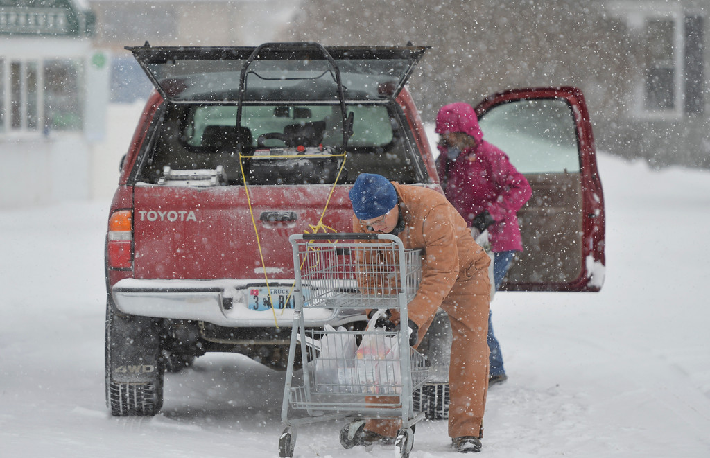 Justin Sheely | The Sheridan Press<br /> Bob Tippie and Denys Tippie load groceries into their truck at Ridley's Friday morning in Sheridan. Snow accumulation reached up to 3 inches Friday morning.