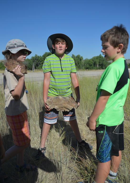 Justin Sheely | The Sheridan Press<br /> Eleven-year-old Coye Gregory, middle, lifts a chunk of petrified wood as Susan Birkholz, left, and Will peterson talk during Science Kids' Rock Talk Wednesday at the Welch Recreation Area off Decker Road. The students learned about the geology of the the Powder River Basin and the Bighorn Mountains, and how it affected the history of humans in the area during the week-long program. Rock Talk is one of many educational programs offered by Science Kids, a nonprofit that makes science learning fun for youth.