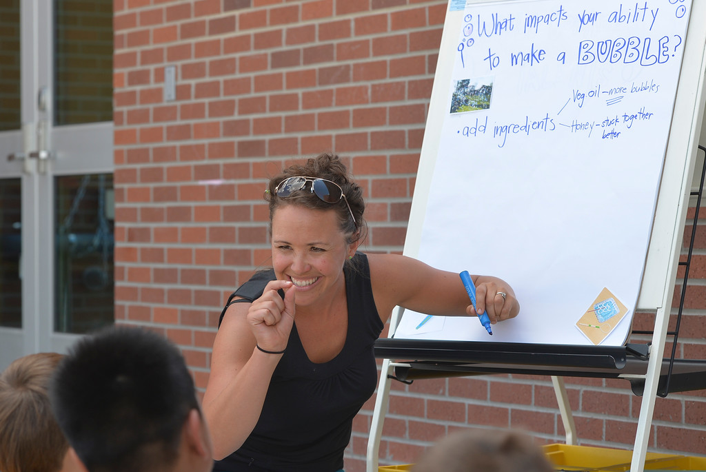 "Justin Sheely | The Sheridan Press<br /> Fourth-grade teacher Mandy Roseberry rights down students' observation on ingredients that worked for making bubbles during Coffeen's Literacy, Leadership and Lots of Science event ""Bubble Bonanza"" Wednesday at Coffeen Elementary School. Literacy, Leadership and Lots of Science is a voluntary summer leadership program offered by Coffeen school teachers Mandy Rose Berry and Shebree Moore to engage children in reading, leadership activities and science experiments. This week's event explored how bubbles are made. The students tried making their own solution by mixing various household ingredients to see what combination made the best bubbles."