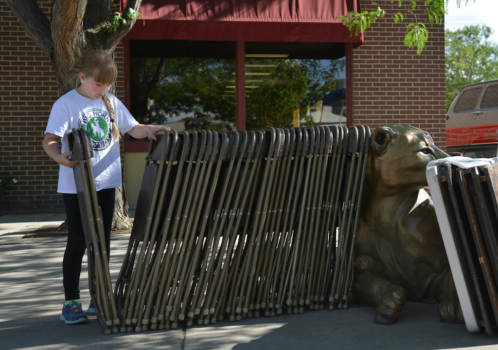 Justin Sheely | The Sheridan Press<br /> Ten-year-old Grace Hinton, volunteering with the Big Horn Cowboys 4-H Club, picks up chairs to set out during the Famers Market Thursday on Grinnell Plaza.