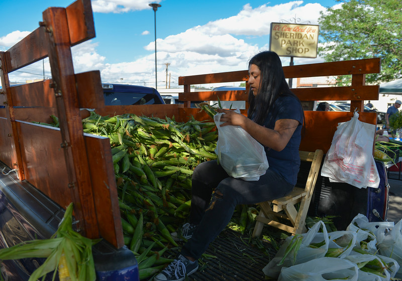 Justin Sheely | The Sheridan Press<br /> Erika Hernandez of Hardin, Montana, fills plastic bags with corn for shoppers during the Famers Market Thursday on Grinnell Plaza.