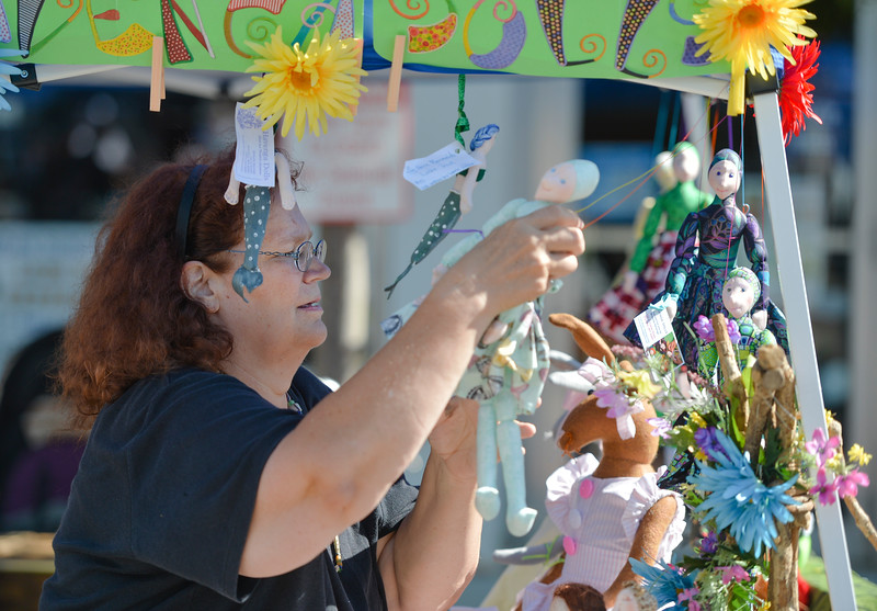 Justin Sheely | The Sheridan Press<br /> Michelle Havenga hangs up dolls at her booth during the Famers Market Thursday on Grinnell Plaza.