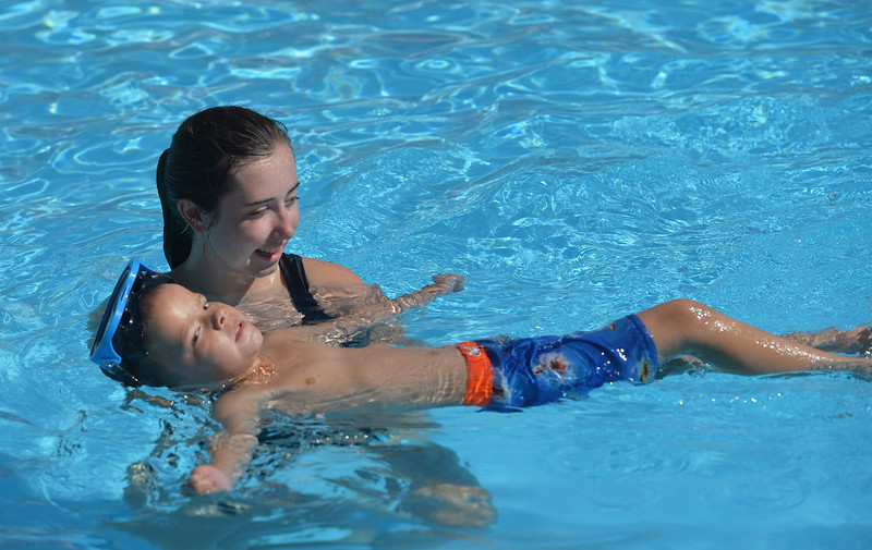 Justin Sheely | The Sheridan Press <br /> Tongue River High School junior Jenna Keller holds Lute Paulsen, 5, as he learns to float on his back during swimming lessons Thursday at the public pool in Dayton. The swim lessons are offered by the town of Dayton and the Tongue River Valley Community Center in two-week long sessions in June and July for kids of various skill levels.
