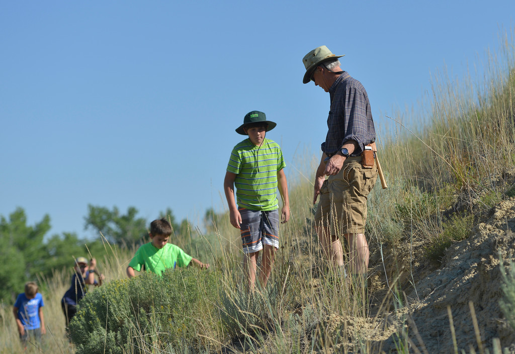 Justin Sheely | The Sheridan Press<br /> Eleven-year-old Coye Gregory follows geology expert Doug Melius up a hill in search for petrified wood during Science Kids' Rock Talk Wednesday at the Welch Recreation Area off Decker Road. The students learned about the geology of the the Powder River Basin and the Bighorn Mountains, and how it affected the history of humans in the area during the week-long program. Rock Talk is one of many educational programs offered by Science Kids, a nonprofit that makes science learning fun for youth.