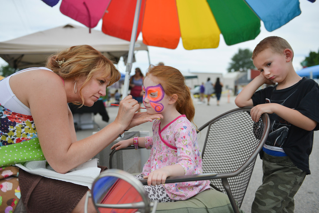 Justin Sheely | The Sheridan Press<br /> Amy Masters, Perfect 10 Nail Studio, Dayton, paints five-year-old Brynlee Wohlers' face as Sam Elchlinger, 4, waits his turn during the Art and Craft Festival Saturday in Dayton.