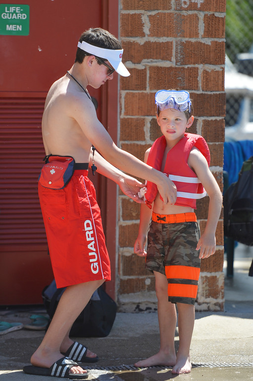 Justin Sheely | The Sheridan Press<br /> Lifeguard Calvin Gilmer helps Rylan Phillips, 7, into a life vest during the opening day of Kendrick Park Pool. Open swim is daily from 1 p.m. to 7 p.m. The pool is also available for private rentals from 7 p.m. to 9 p.m.