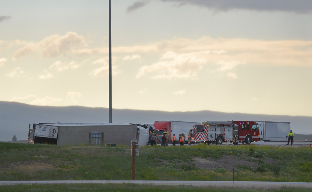 Justin Sheely | The Sheridan Press<br /> Emergency personnel respond after a commercial truck was toppled by strong winds as it was approaching the weighing station at the Wyoming port of entry Thursday evening just off I-90 north of Sheridan. Rocky Mountain Ambulance and Tongue River Fire District responded to the call approximately 5:39 p.m. Thursday and later called for Sheridan Fire-Rescue to extricate the driver from the truck's cabin. Wyoming Highway Patrol also responded to the call. The truck driver Clayton Winters of Mississippi walked away from the scene with only a scrape to the leg. No other persons were injured. The truck was pulling an empty trailer and driving under 10mph at the time it was blown over, according to Winters. The National Weather Service in Billings reported wind gusts up to 62mph during Thursday's evening storm.