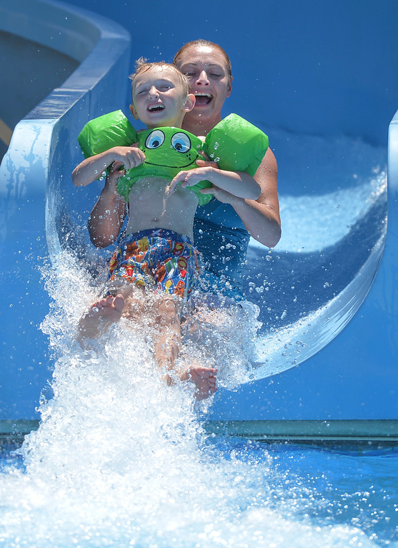 Justin Sheely | The Sheridan Press<br /> Dana Turner rides down the waterslide with five-year-old son Ayden Turner on the opening day of Kendrick Park Pool. Open swim is daily from 1 p.m. to 7 p.m. The pool is also available for private rentals from 7 p.m. to 9 p.m.