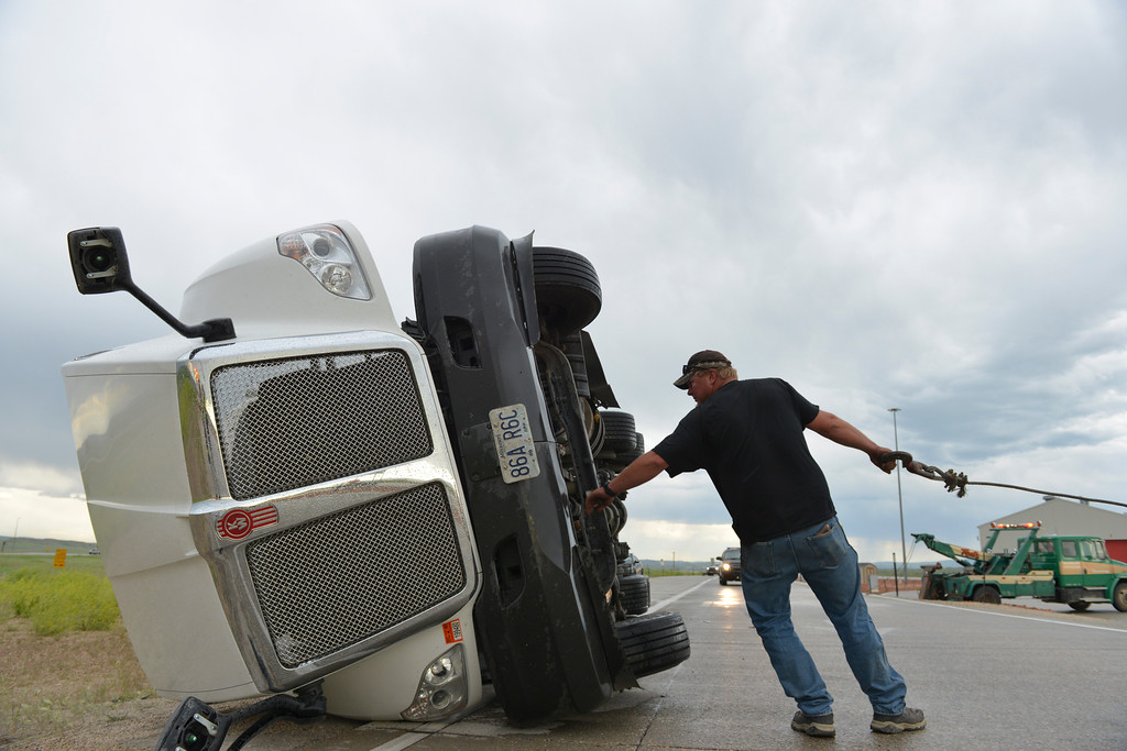 Justin Sheely | The Sheridan Press<br /> A man from Ted's Towing pulls a cable to the commercial truck after it was toppled by strong winds as it was approaching the weighing station at the Wyoming port of entry Thursday evening just off I-90 north of Sheridan. Rocky Mountain Ambulance and Tongue River Fire District responded to the call approximately 5:39 p.m. Thursday and later called for Sheridan Fire-Rescue to extricate the driver from the truck's cabin. Wyoming Highway Patrol also responded to the call. The truck driver Clayton Winters walked away from the scene with only a scrape to the leg. No other persons were injured. The truck was pulling an empty trailer and driving under 10mph at the time it was blown over, according to Winters. The National Weather Service in Billings reported wind gusts up to 62mph during Thursday's evening storm.