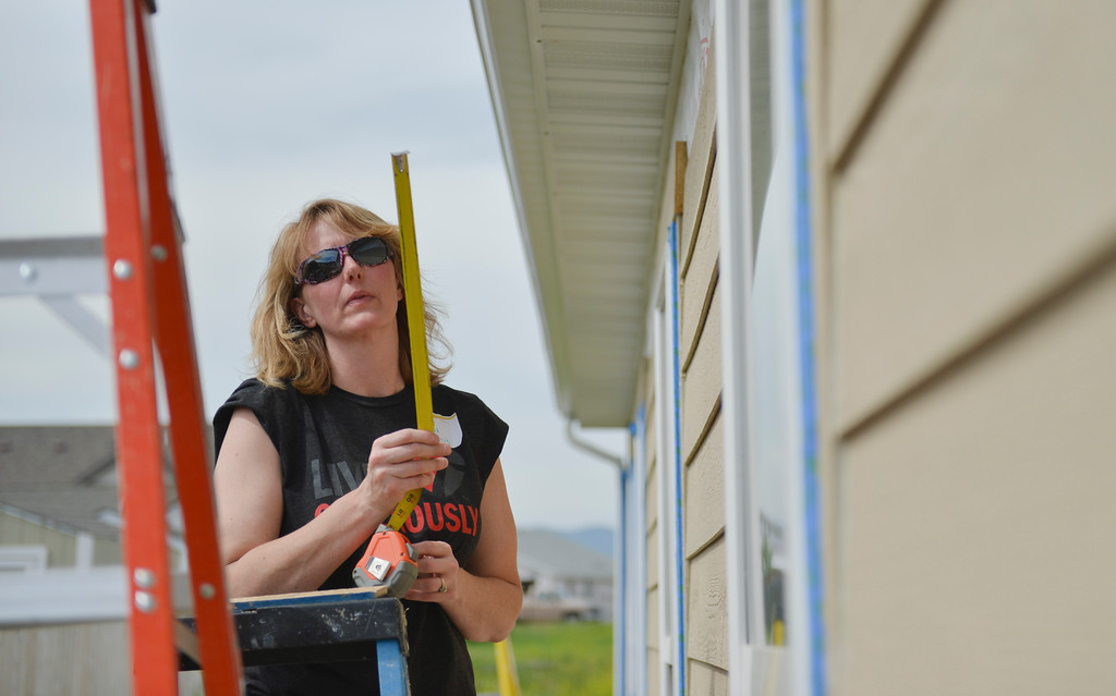 Justin Sheely | The Sheridan Press<br /> Volunteer Renae Morris measures a cut for siding during Habitat for Humanity of the Eastern Bighorns Women Build day Saturday at Poplar Grove in North Sheridan. The event was a volunteer effort for women only to help build a habitat home for local resident Kathy Baker and her four children. The home is designed to be handicap accessible for on of Baker's children who requires wheelchair access. The home features extra-wide doors and an extra wide bath tub.