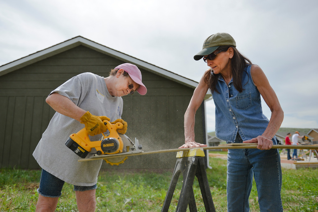 Justin Sheely | The Sheridan Press<br /> Volunteers Connie Goodwin, left, cuts a piece of siding as Sherry Mercer stabilizes it during Habitat for Humanity of the Eastern Bighorns Women Build day Saturday at Poplar Grove in North Sheridan. The event was a volunteer effort for women only to help build a habitat home for local resident Kathy Baker and her four children. The home is designed to be handicap accessible for on of Baker's children who requires wheelchair access. The home features extra-wide doors and an extra wide bath tub.