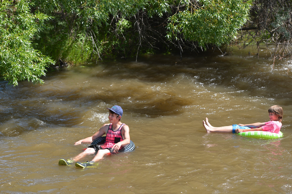Justin Sheely | The Sheridan Press<br /> Sixteen-year-old Tyler Wilkerson, left, and Blaize Nixon, 12, float down the Little Goose at Sheltered Acres Park Tuesday afternoon. Tuesday saw a high temperature of 90-degrees fahrenheit. Temperatures will peak in the low 90s through the weekend.