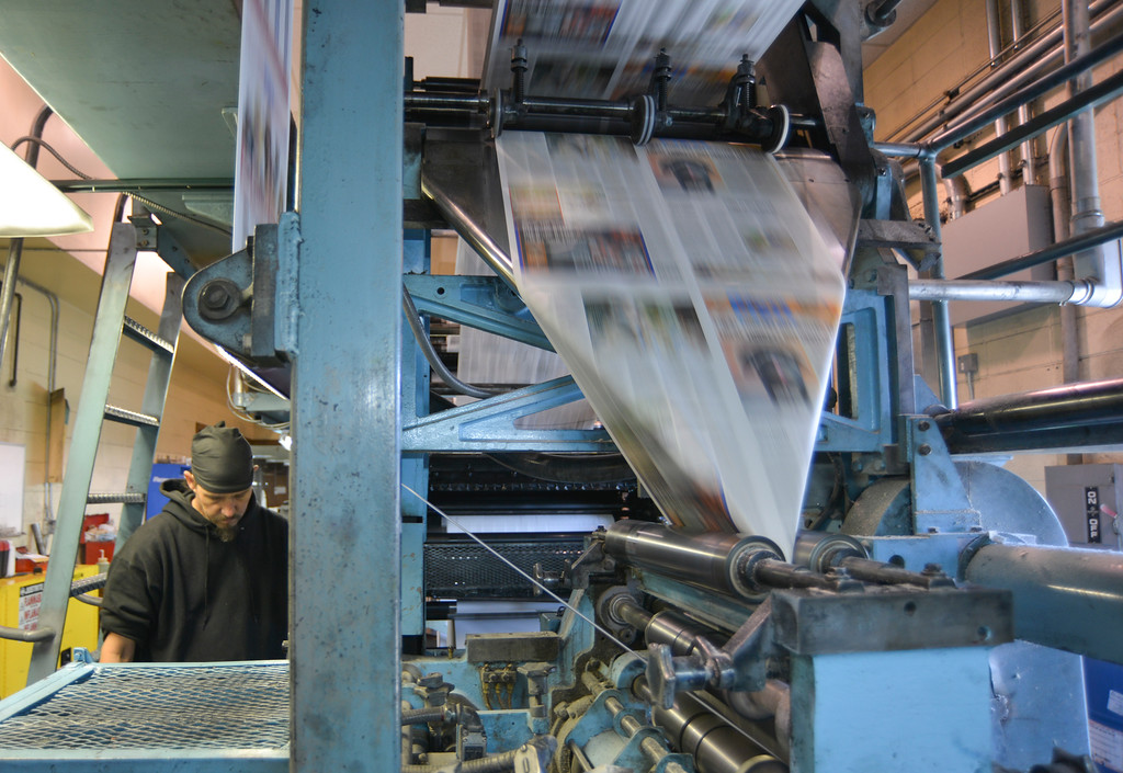 Justin Sheely | The Sheridan Press<br /> Thomas Miller checks the print quality as paper rolls on through the printing press for the county-wide free distribution of the Thanksgiving Day paper Wednesday at The Sheridan Press. More than 12,000 papers were distributed to homes across Sheridan County for the free edition of The Sheridan Press.