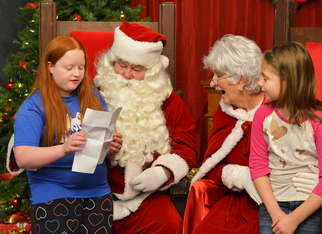 Justin Sheely | The Sheridan Press<br /> Ten-year-old Anastacia Graves, left, reads off her wish list to Santa Claus as her friend Vivian Hedstrom looks on during the annual Christmas Stroll Friday on Main Street. The event is to encourage the community to shop local and and provides fun activities for children, including wagon rides and pictures with Santa.