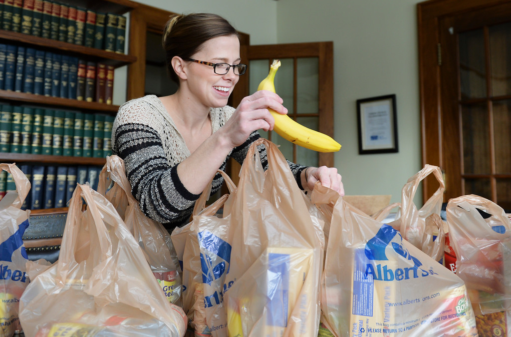 Justin Sheely | The Sheridan Press<br /> Volunteer Alyssa Davis fills sacks with fruit at Barney and Graham Monday morning for the Thanksgiving Day distribution.