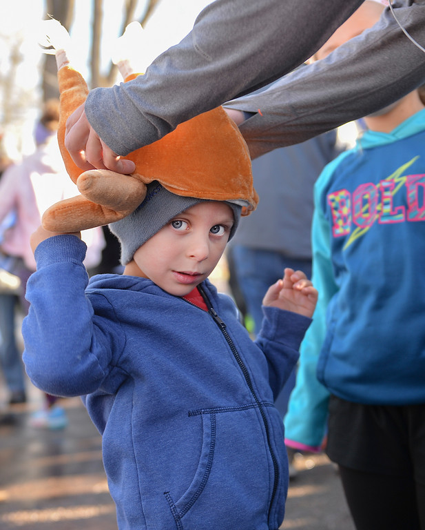 Justin Sheely | The Sheridan Press<br /> Four-year-old Luke Johnson looks on as his father snugs down his turkey hat prior to the 38th annual Turkey Trot Thursday morning at Kendrick Park. Proceeds from the event support the Sheridan Junior High School and Sheridan High School Cross Country and Track and Field programs.